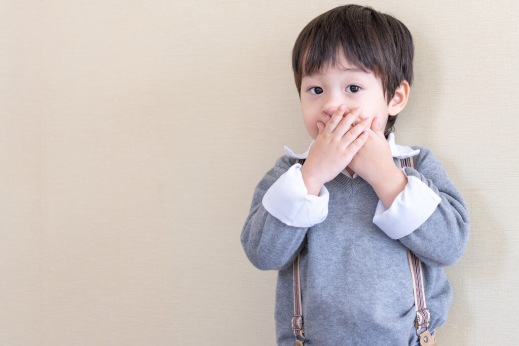 Young Boy Holding Hands Over Mouth